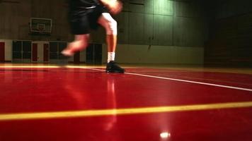 niedriger Winkel, während ein Basketballspieler nach vorne dribbelt und springt, um einen Korb zu schießen