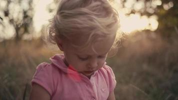 A cute little girl in a field holding an apple and offering it to the camera, with lens flare video