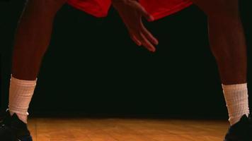 un giocatore di basket dribbla la palla verso il basso su uno sfondo nero, da vicino