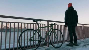 Guy with fixed gear bike staying on marine station and looking at sea port, 4k video