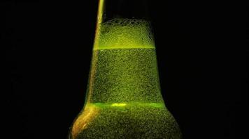 Ein grüner Flaschenhals mit vielen Blasen ist auf schwarzem Hintergrund video