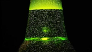 da vicino: un collo di bottiglia verde con molte bolle è su sfondo nero