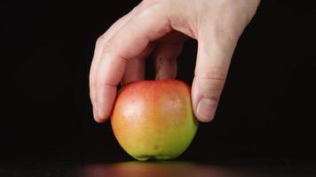 menschliche Hand nimmt eine Hälfte des roten Apfels weg