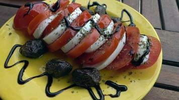 queso mozzarella con tomate, aceitunas secas, crema balsámica y aceite
