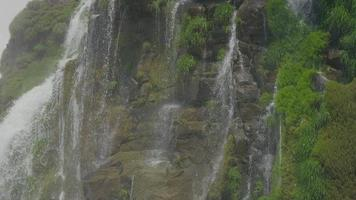 cascada en medio de las montañas con árboles y rocas en resolución 4k video