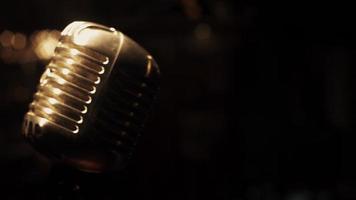 microfono da concerto bagliore di metallo stare sul palco nel club retrò. faretti. Vintage ▾