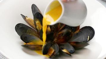 Krug gießt Sauce auf Muscheln. video