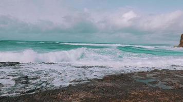Ozeanwellen, die am Steinstrand ankommen video