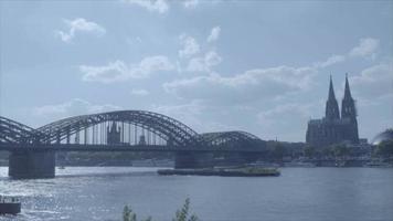 barco com lapso de tempo passando pela catedral de Colônia e sob a ponte / rio Reno Hohenzollern em 4k e slog3. koelner dom. Tiro longo. video