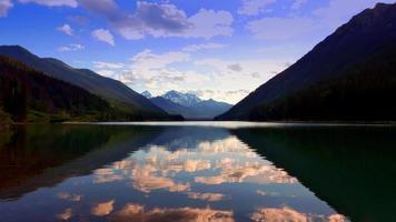 Bergseelandschaft, bunte Reflexion und Silhouette untergehende Sonne