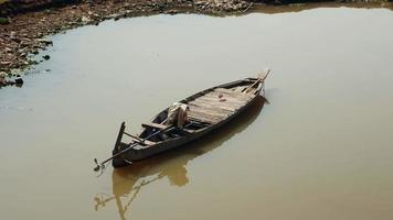pequeno barco de pesca de madeira flutuando na água