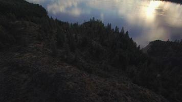 Revelación aérea cinematográfica épica de nubes dispersas sobre el lago con misty mountai