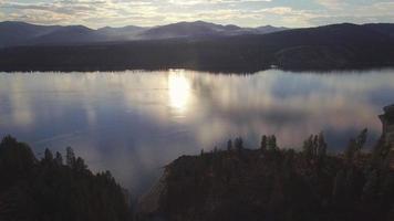 Pan aéreo del lago Roosevelt al atardecer con reflejo de nubes sobre el agua