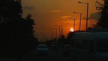 gesperrter Schuss des Verkehrs, der auf Straße bei Sonnenuntergang, Delhi, Indien bewegt video