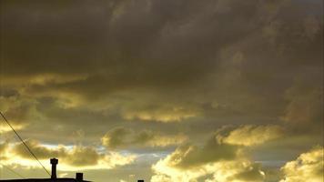 nubes grises y amarillas nadando sobre el techo del edificio. la luz del sol se refleja en las nubes. día nublado de otoño en la puesta del sol. video