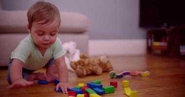 Bébé garçon mâchant un bloc de construction coloré