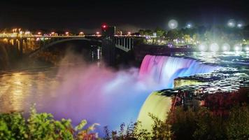Niagara Falls at night. The jets of falling water are illuminated with colored spotlights. Exquisitely beautiful sight - popular among tourists