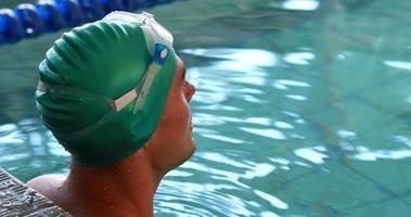 Fit Schwimmer lächelt in die Kamera im Schwimmbad