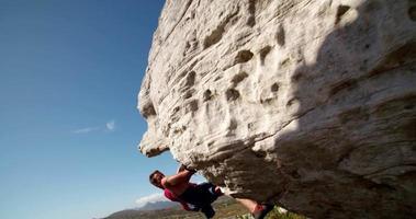 alpinista segurando uma pedra e focando na rota video