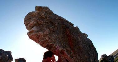 alpinista subindo na saliência escalando até o topo