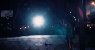 giocatore di basket che si esercita da solo in campo di notte