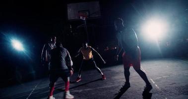 giocatori di basket che giocano in tribunale durante la notte