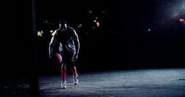 Basketballspieler, der Nachtball auf dem Platz hüpft