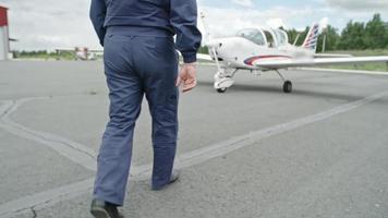 reifer Pilot, der in Richtung Flugzeug geht
