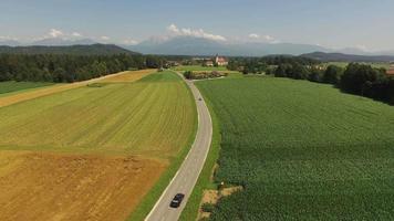 Kamera fliegt über Straße in einem schönen Feld