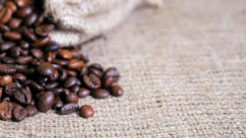 Coffee beans spilled from pouch on sackcloth. Dolly shot. video