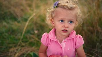 una bambina carina in un campo con in mano una mela