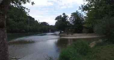 sorvolando un fiume fino a un ponte dove passa un treno
