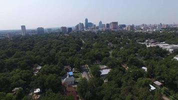 vista aérea de um bairro residencial cercado por muita vegetação e edifícios ao fundo - Austin, Texas, EUA video