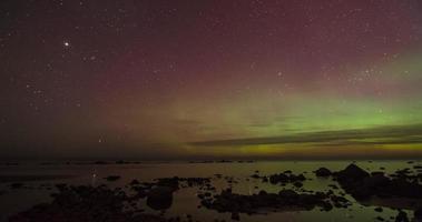 Zeitrafferpfanne von Aurora Borealis (Nordlichter) an einem felsigen Meer