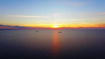 zwei Boote, die bei Sonnenuntergang im Meer schwimmen