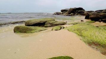 ondas suaves com uma costa rochosa e praia arenosa.