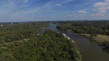 vista aerea della telecamera in movimento verso il fiume fiancheggiato da alberi da alta quota