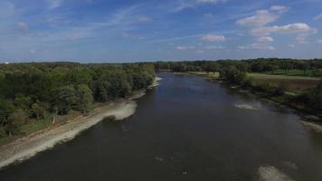 câmera de vista aérea movendo-se sobre um rio ladeado de árvores em um dia calmo