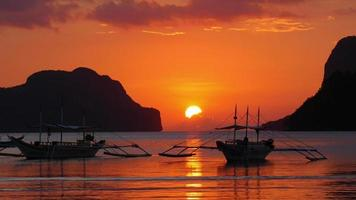 Hochwertige Aufnahme traditioneller philippinischer Boote in der Bucht von El Nido bei Sonnenuntergangslichtern. Palawan Island, Philippinen