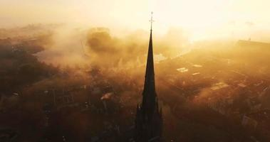 Camera tilts down showing a cross on top of a Christian church covered in fog