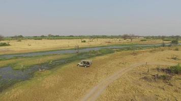 veículo de safári turístico dirigindo ao longo das vias aquáticas do delta do okavango