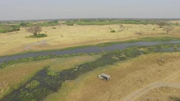 veicolo safari turistico che guida lungo le vie d'acqua del delta dell'okavango