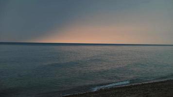 bella pendenza nel cielo mentre il sole tramonta sulle onde calme del lago Michigan video