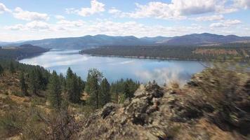 dolly aérea fotografada por rochas do deserto para revelar um grande lago com colinas video