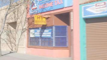 guidando oltre le vetrine colorate dei negozi della città di confine video