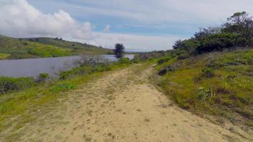 sentier de survol aérien, puis étang, puis boum pour révéler les terres agricoles et l'océan pacifique en arrière-plan 4k stabilisé video