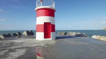 Gehen Sie in der Nähe des Leuchtturms auf dem Wellenbrecher video
