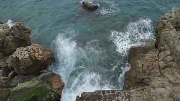 Upper view sea with waves breaking and frothing on a rocky beach