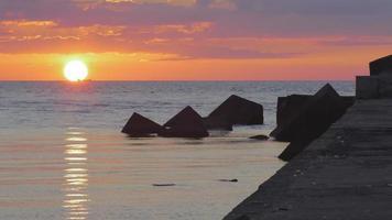 sole che tramonta dietro una nave portarinfuse su un mare calmo