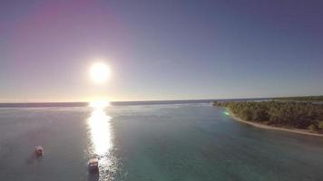 Aerial view over a tropical lagoon with boats in clear blue water during sunrise hour - Tetiaroa, Tahiti, French Polynesia video